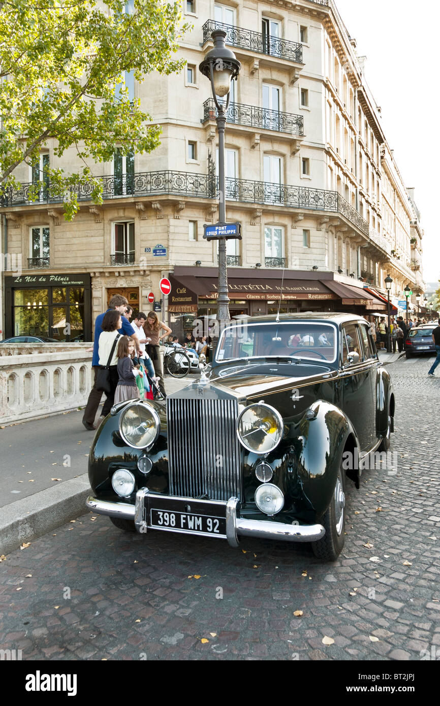 weekend Parisian street life goes on around magnificent gleaming old Rolls Royce parked on Pont Louis Philippe in - Stock Image
