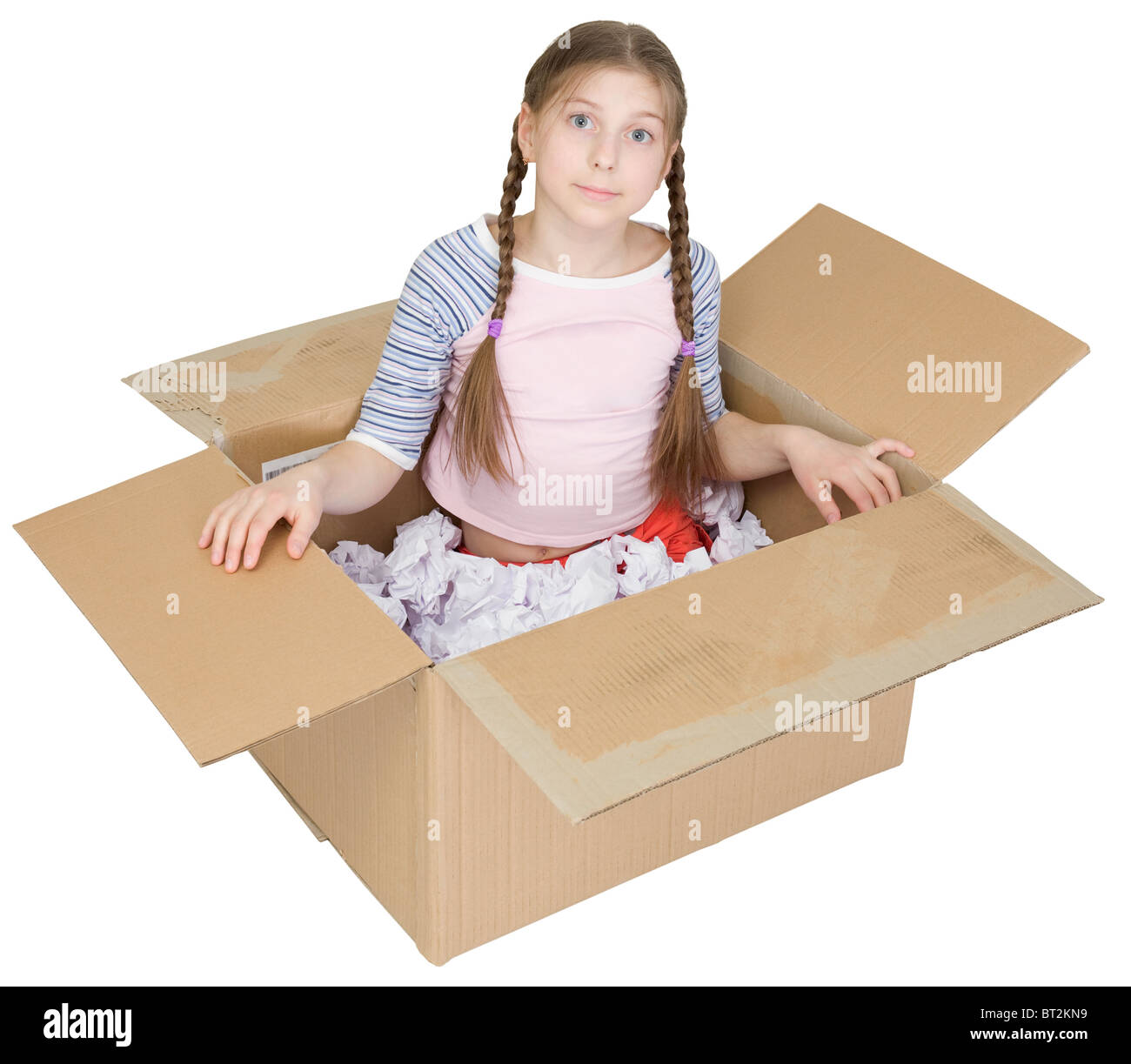 The little girl sits in a cardboard box - Stock Image