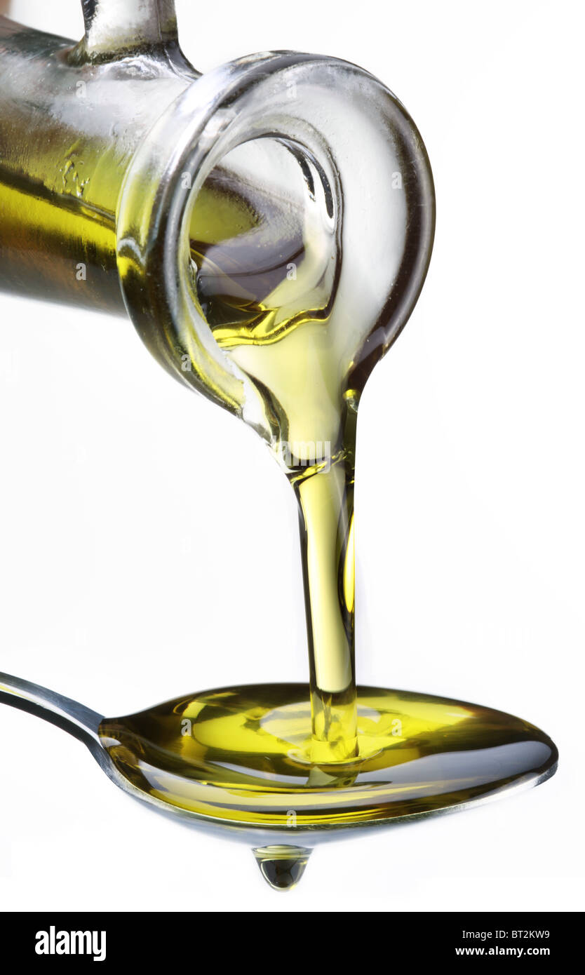 a365f7c38bf585 Olive oil flowing from carafe into the spoon isolated on a white. - Stock  Image