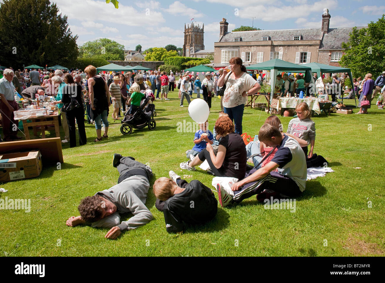 A family sits on the grass at the annual summer Charminster Fete, in the Dorset village of Charminster. DAVID MANSELL - Stock Image
