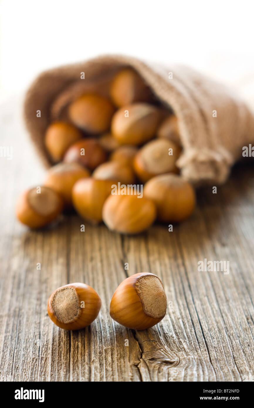 Ripe hazelnuts on wooden desk - Stock Image
