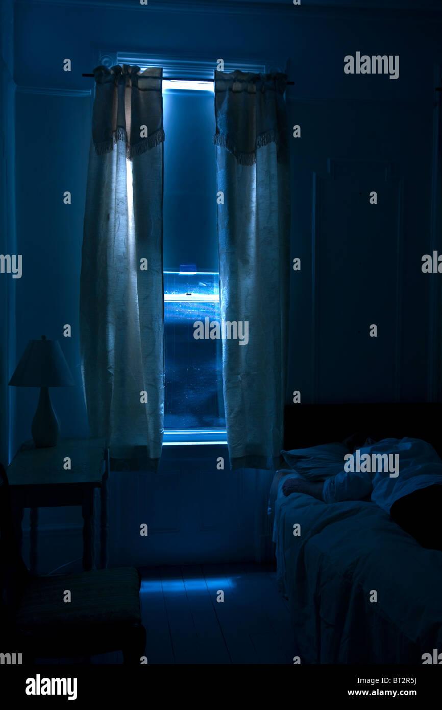 interior hotel room , man sleeping, monochromatic, dark, mystery, suspense,night - Stock Image