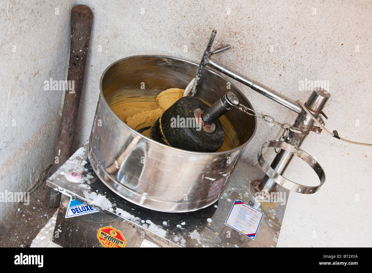 Motorized grinder by an indian house grinding dal and jaggery for preparation of indian sweets at festival time. - Stock Image