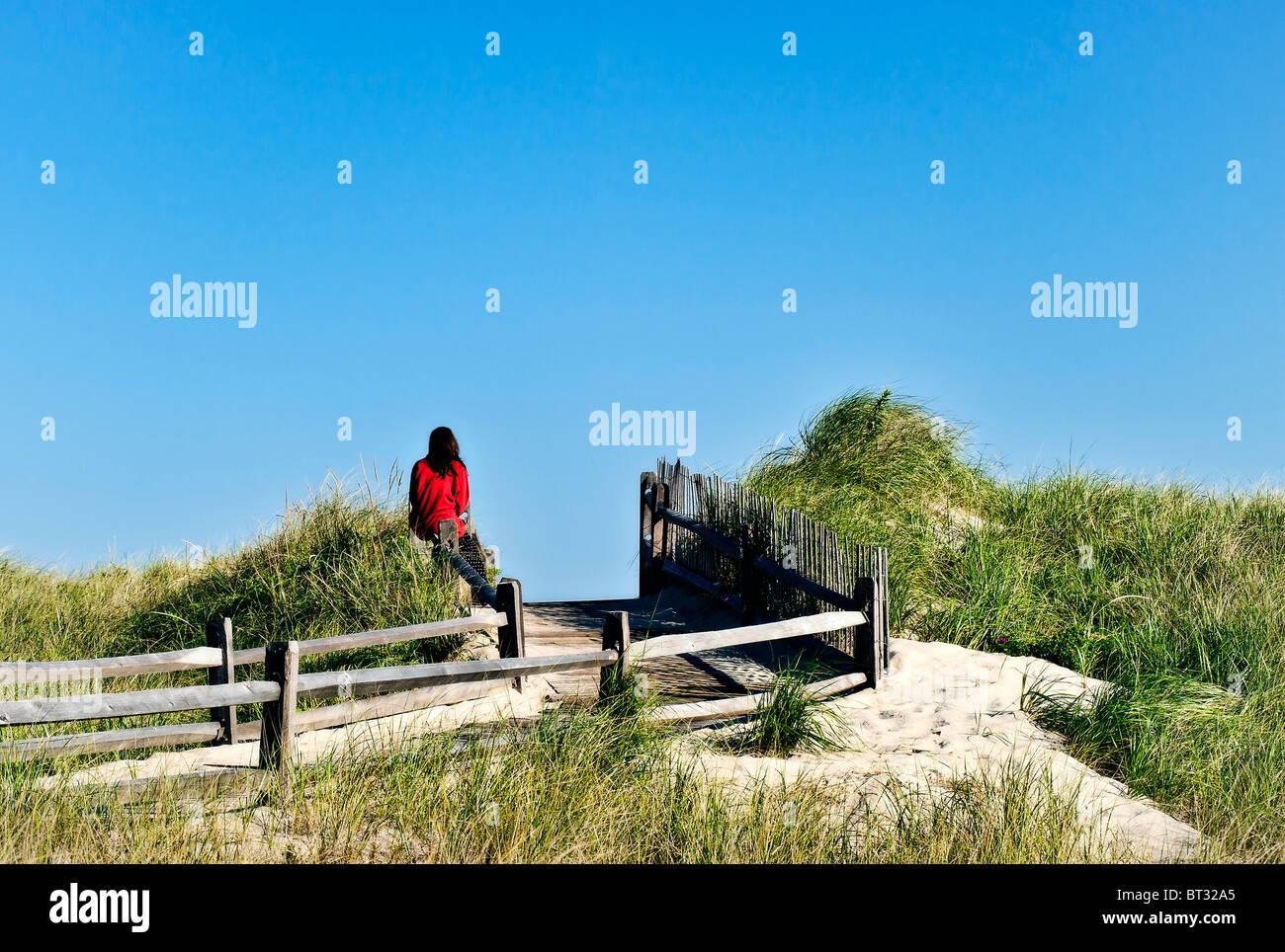 Woman enjoys dune view of the ocean. - Stock Image