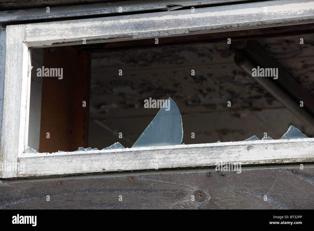 Broken window with glass fragments remaining. - Stock Image