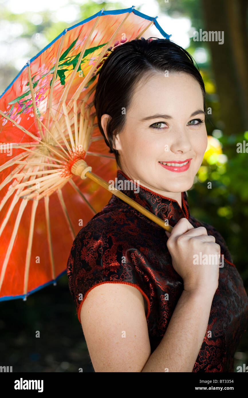 7e0f701429a beautiful young woman in Chinese dress holding a Chinese umbrella - Stock  Image