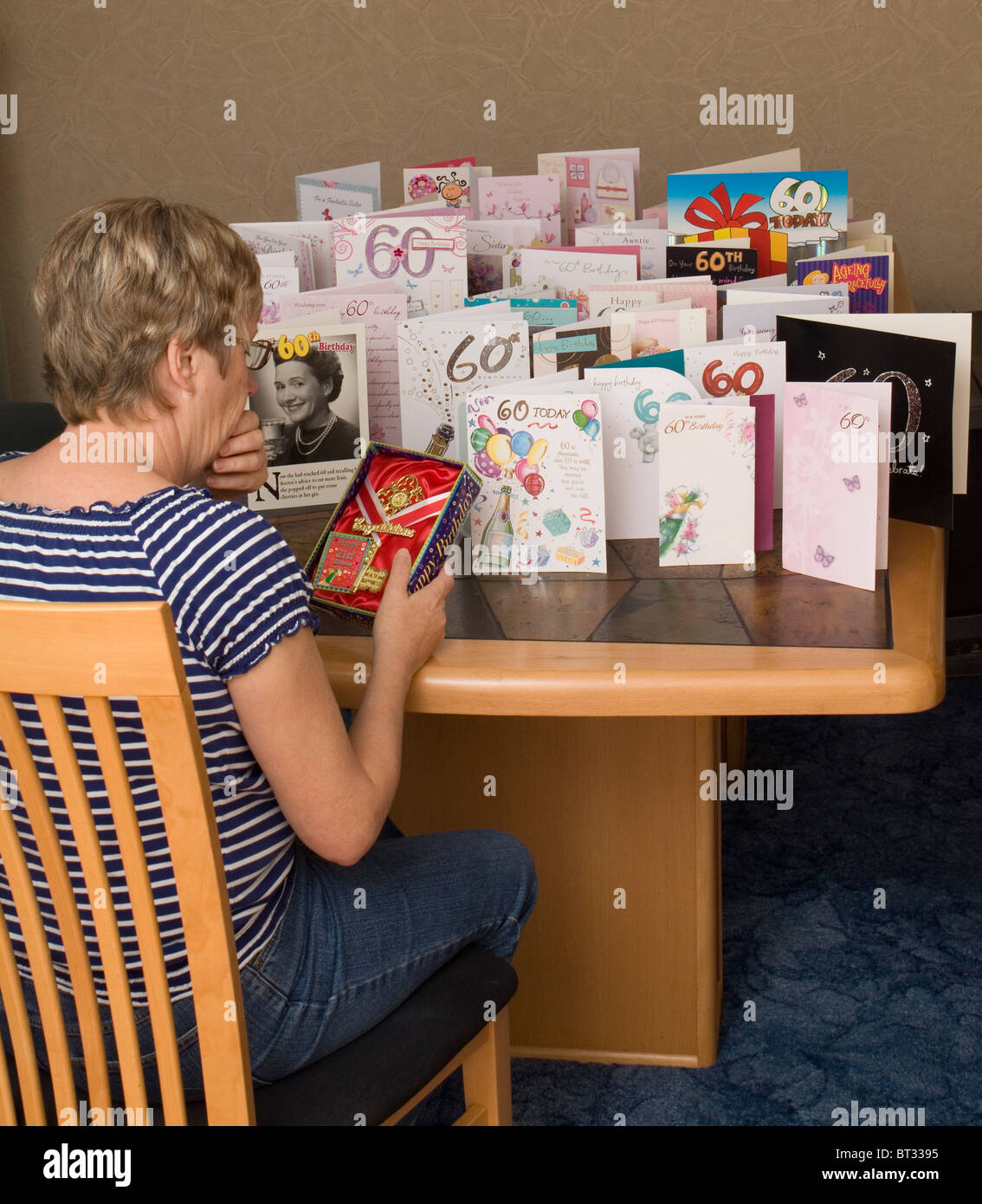 A woman looks depressed while looking at her 21st birthday 'key' while surrounded by cards celebrating her - Stock Image