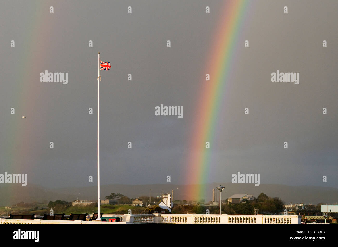 Primary and secondary rainbows during shower at Plymouth Hoe with Union Flag flying from flagpole, Devon UK - Stock Image