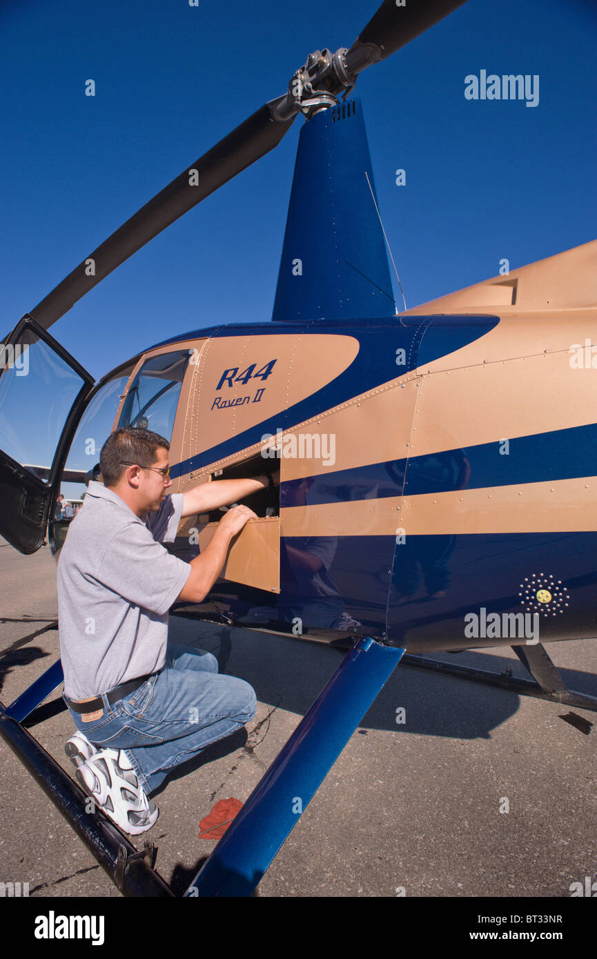 A pilot does his preflight check on a helicopter, at the Ruidoso Mountain High Fly In, Ruidoso, New Mexico. - Stock Image