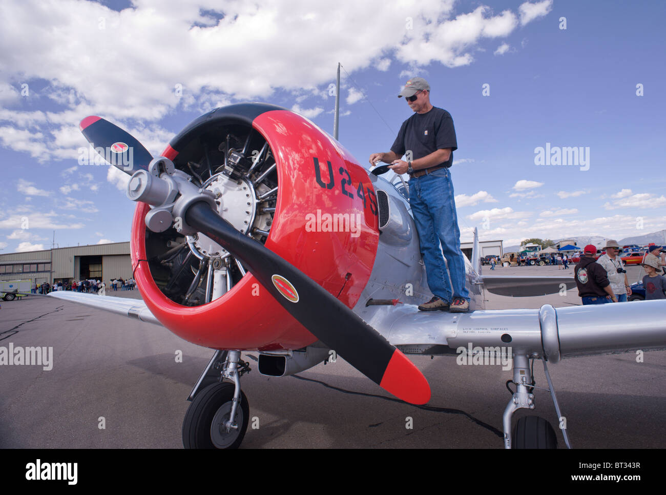 Pilot does a preflight inspection of his T-6 aircraft , at the Ruidoso Mountain High Fly In, Ruidoso, New Mexico. - Stock Image
