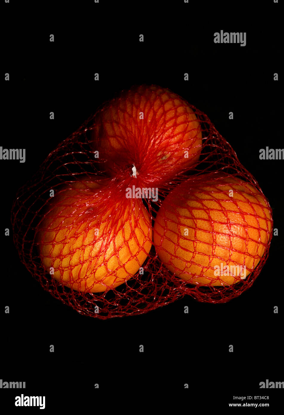 Three oranges isolated on a black background - Stock Image