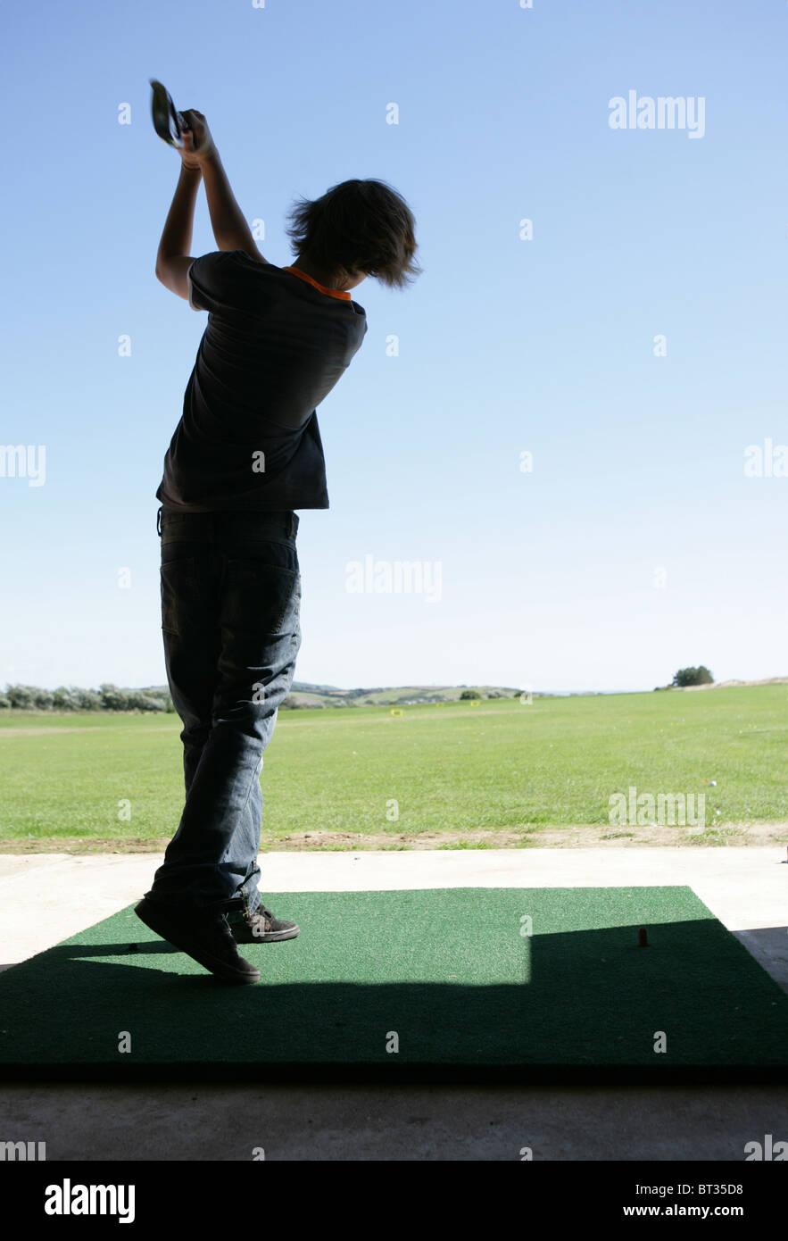 Teenage boy at driving range - Stock Image