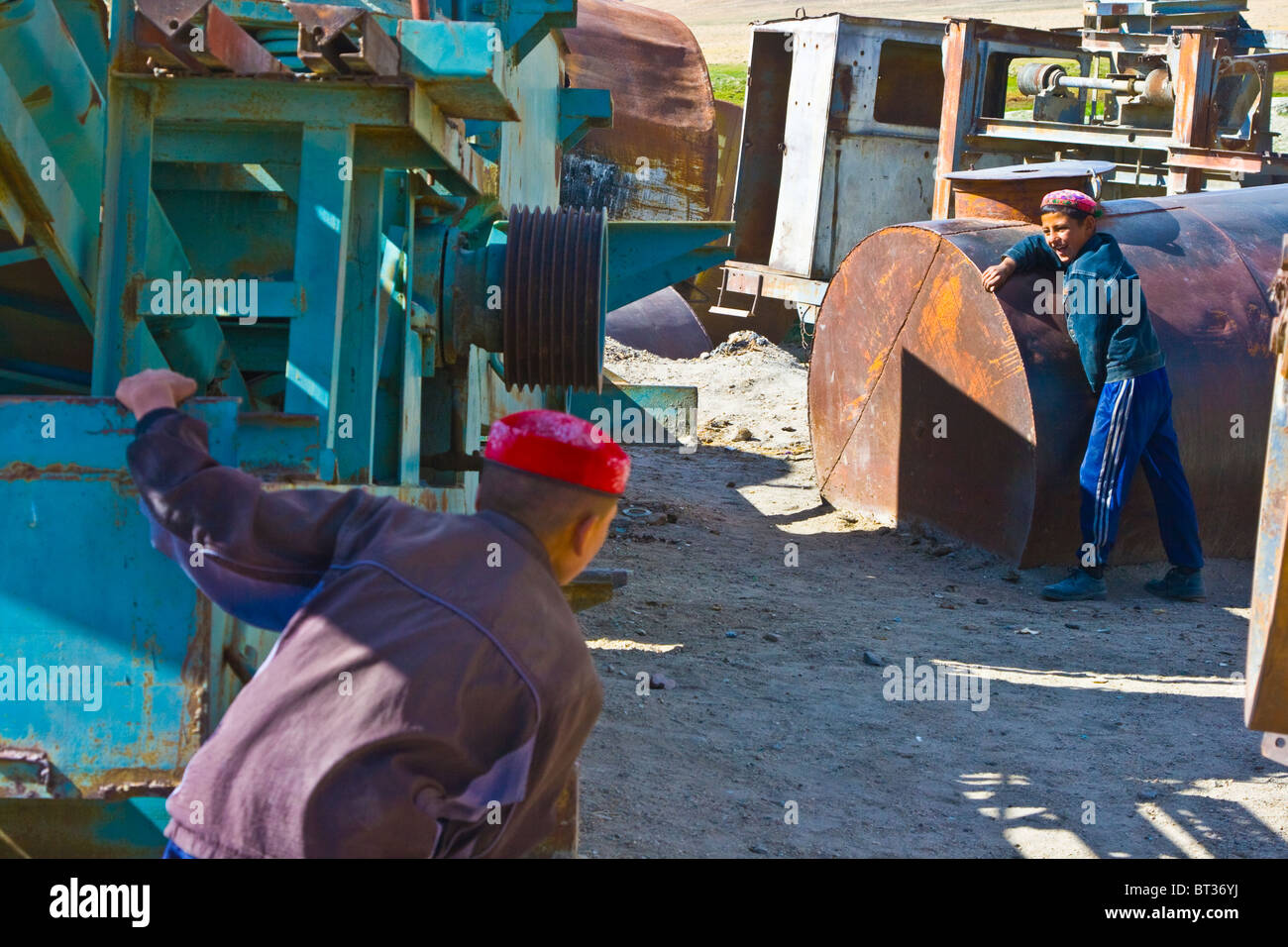 Boys playing hide n seek around rusted equipment in Bulunkul, Pamirs, Tajikistan - Stock Image