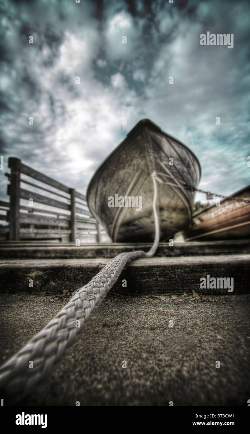 Tethered row boat on shore with long rope - Stock Image