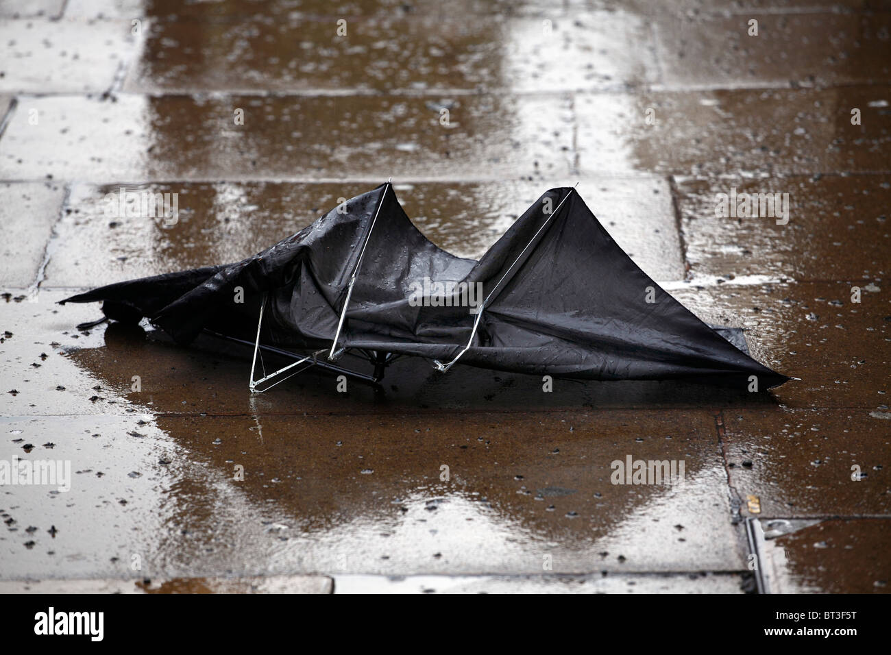 Discarded broken Umbrella in the wet - Stock Image