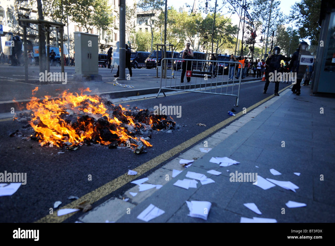 Garbage bags set ablaze in the clashes at the Barcelona city center during the general strike in Spain. - Stock Image
