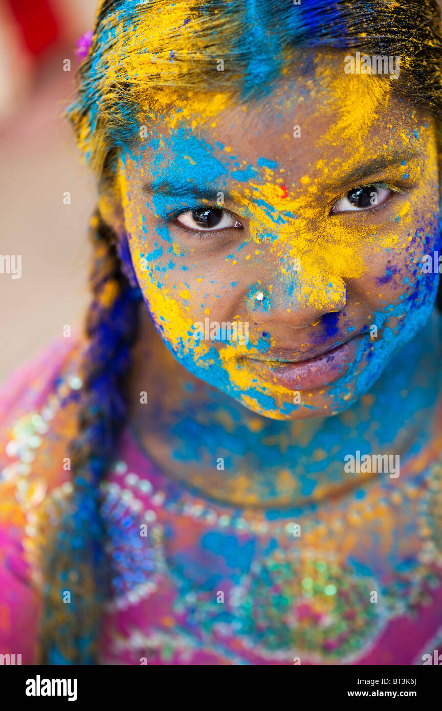 Young Indian girl covered in coloured powder pigment. India - Stock Image