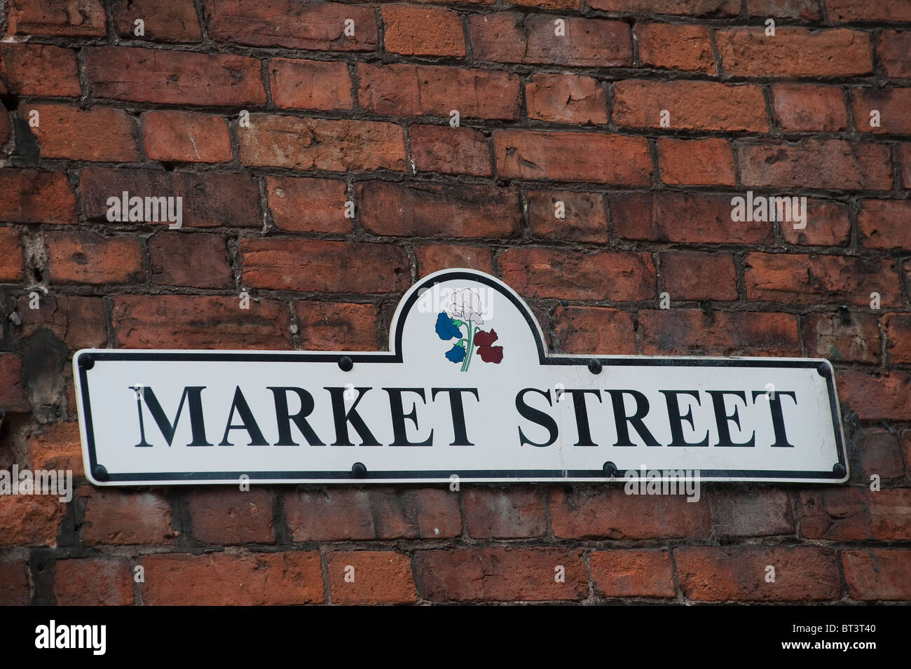 Street sign fixed to a brick wall in an English town. - Stock Image