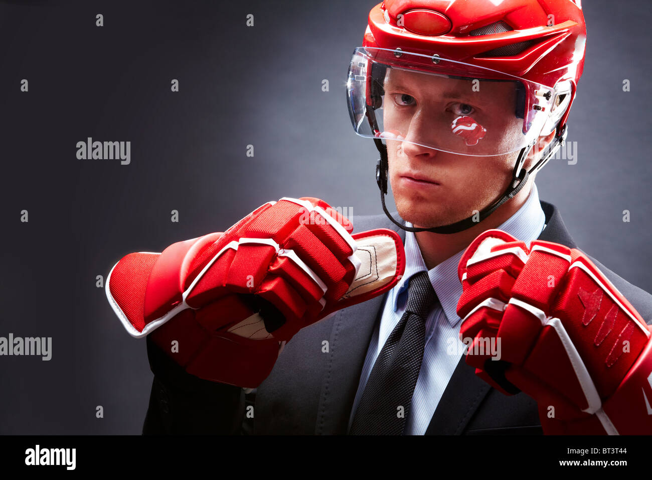 Portrait of sportsman in suit, red gloves and helmet - Stock Image