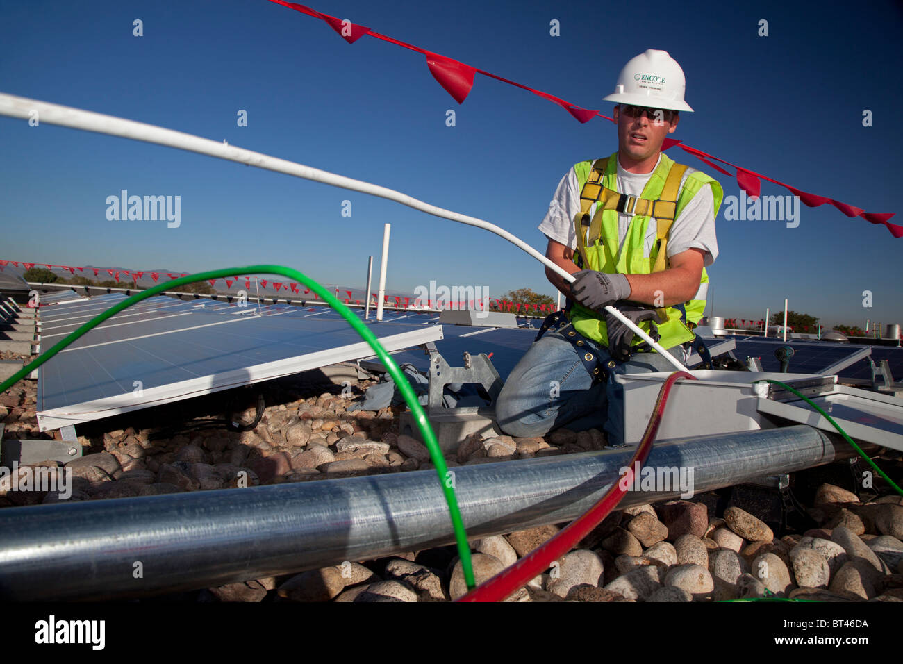 Denver, Colorado - Workers install wiring for solar photovoltaic panels on the roof of Harrington Elementary School. - Stock Image
