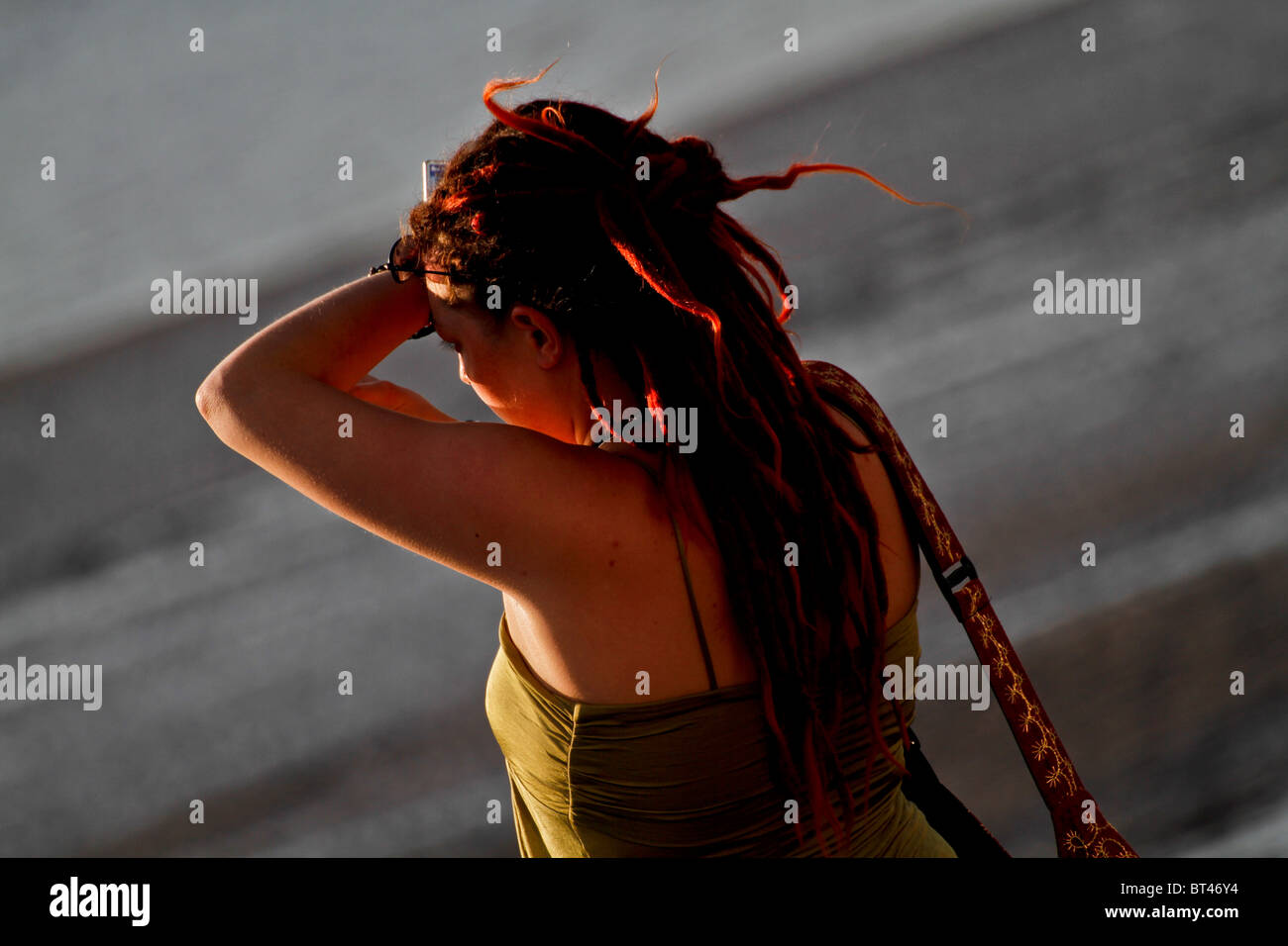 back view of young lady looking at the sunset, holding her arm up to cover her face from the sun - Stock Image