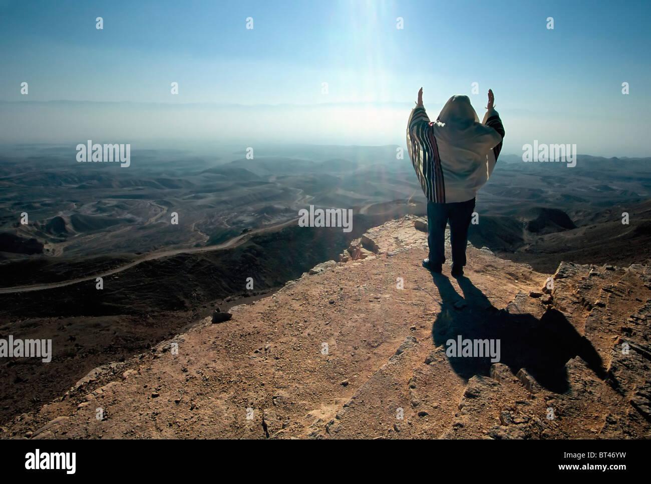 Israel, Negev Desert, Jewish man praying in front of an awe inspiring landscape at dawn, - Stock Image