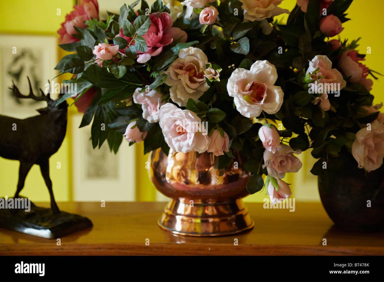 Still life with a bouquet of peony fake flowers in an old copper still life with a bouquet of peony fake flowers in an old copper vase on a shelf indoor interior shot izmirmasajfo Images