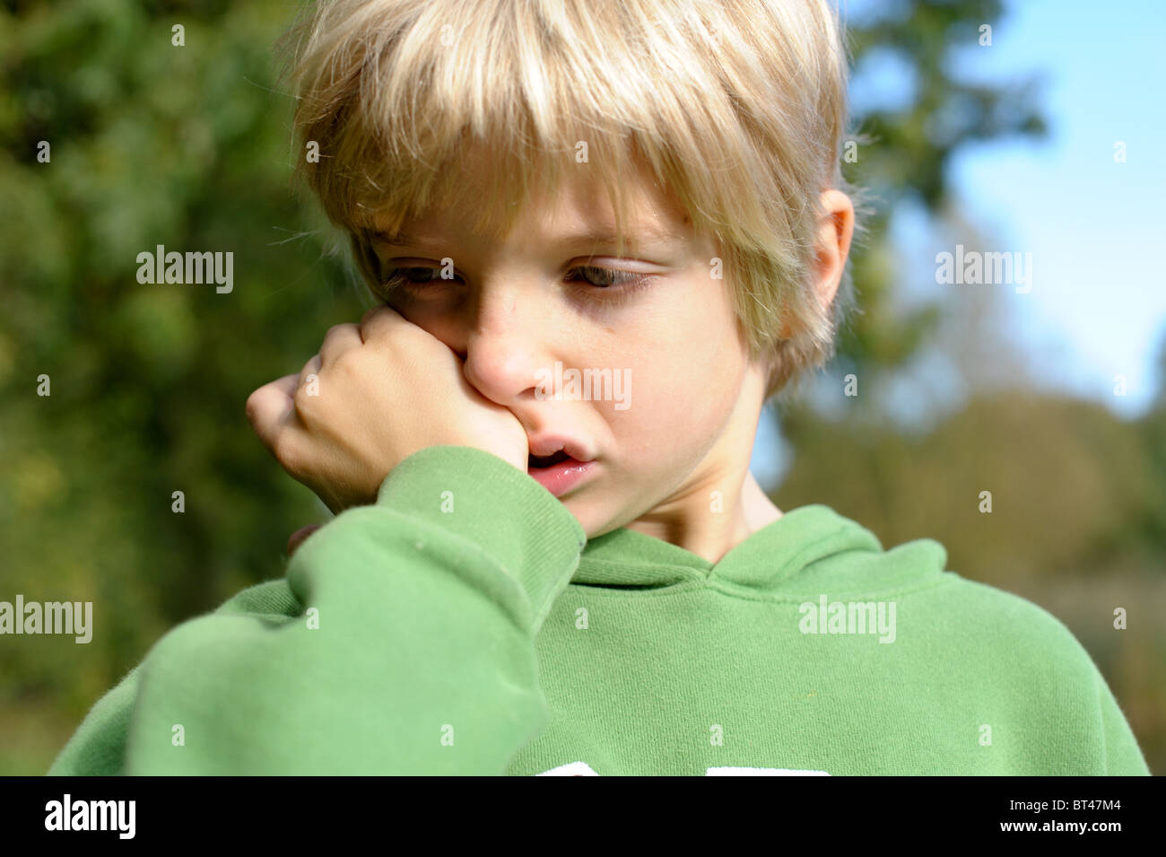 Sad, tired and tearful blond-haired little boy in a green top standing outside alone after being bullied by friends - Stock Image