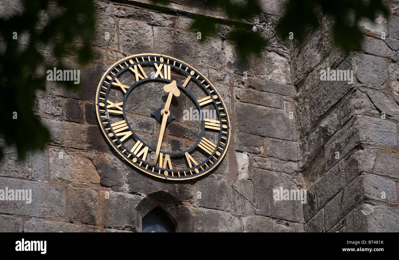 Clock with roman numerals on the outside of a church in an English town - Stock Image