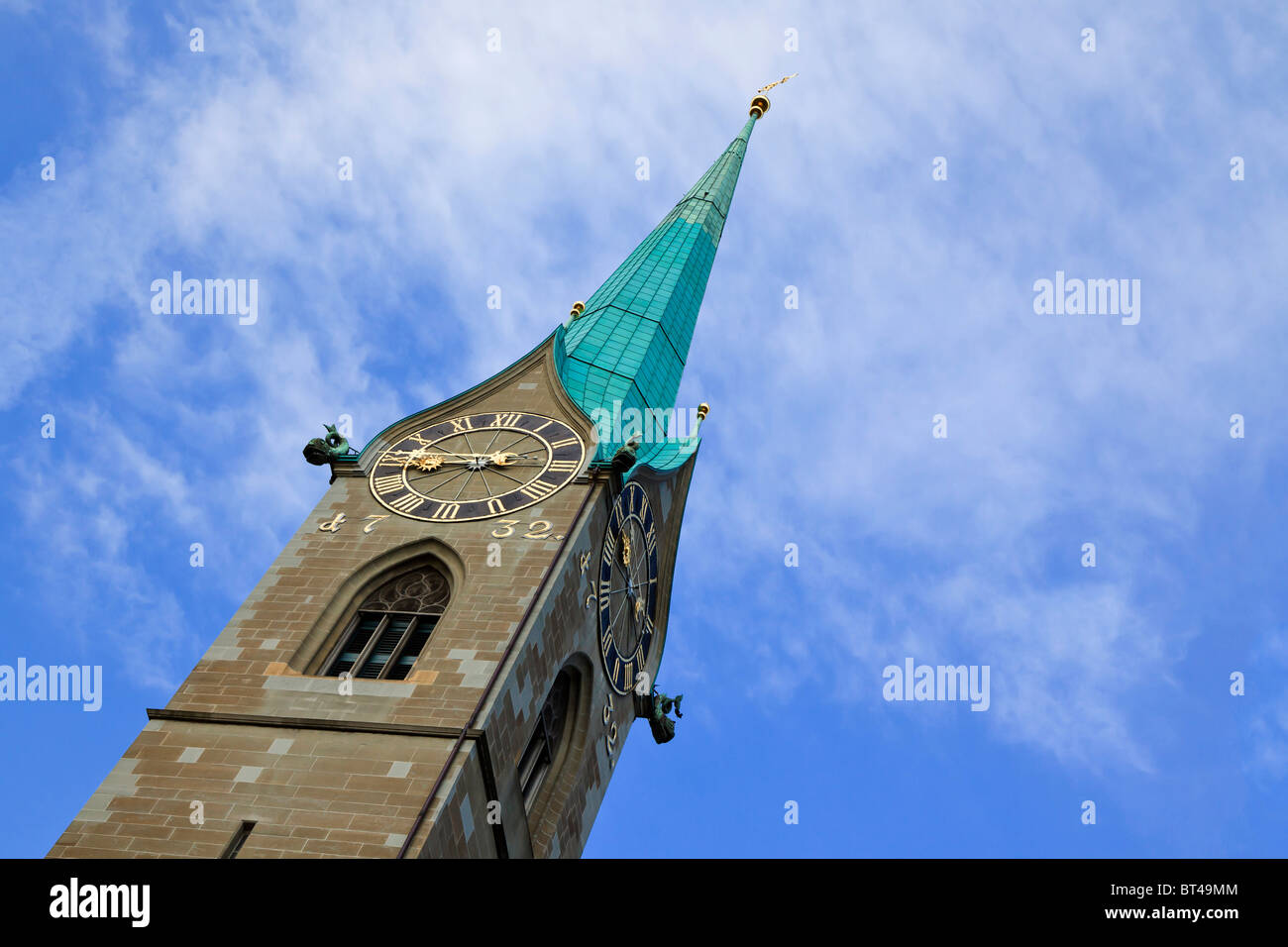 The spire of fraumunster Abbey at an angle against a blue sky. Zurich, Switzerland - Stock Image