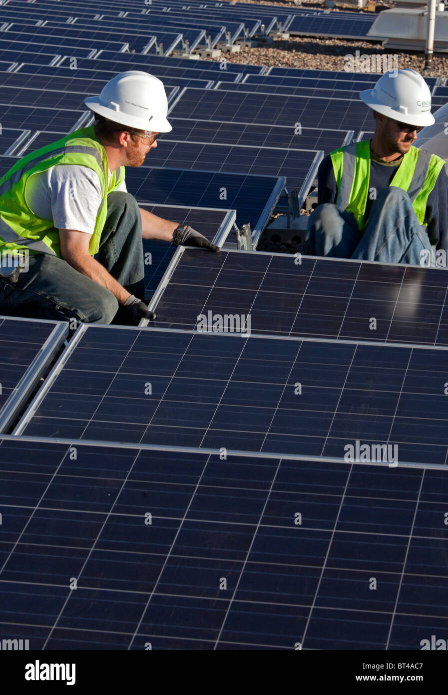 Denver, Colorado - Workers install solar photovoltaic panels on the roof of Harrington Elementary School. - Stock Image