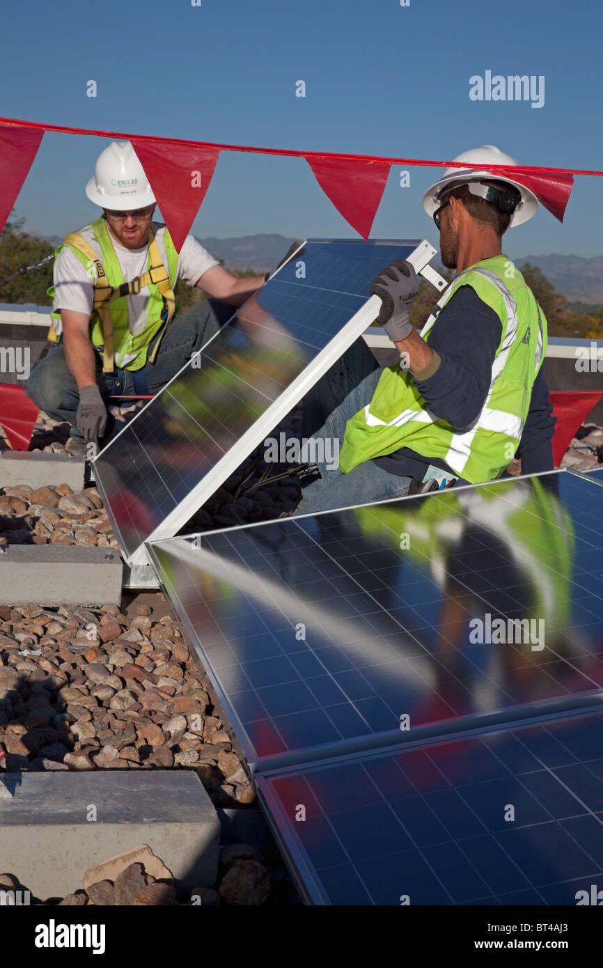 Workers Install Solar Panels on Roof of an Elementary School - Stock Image