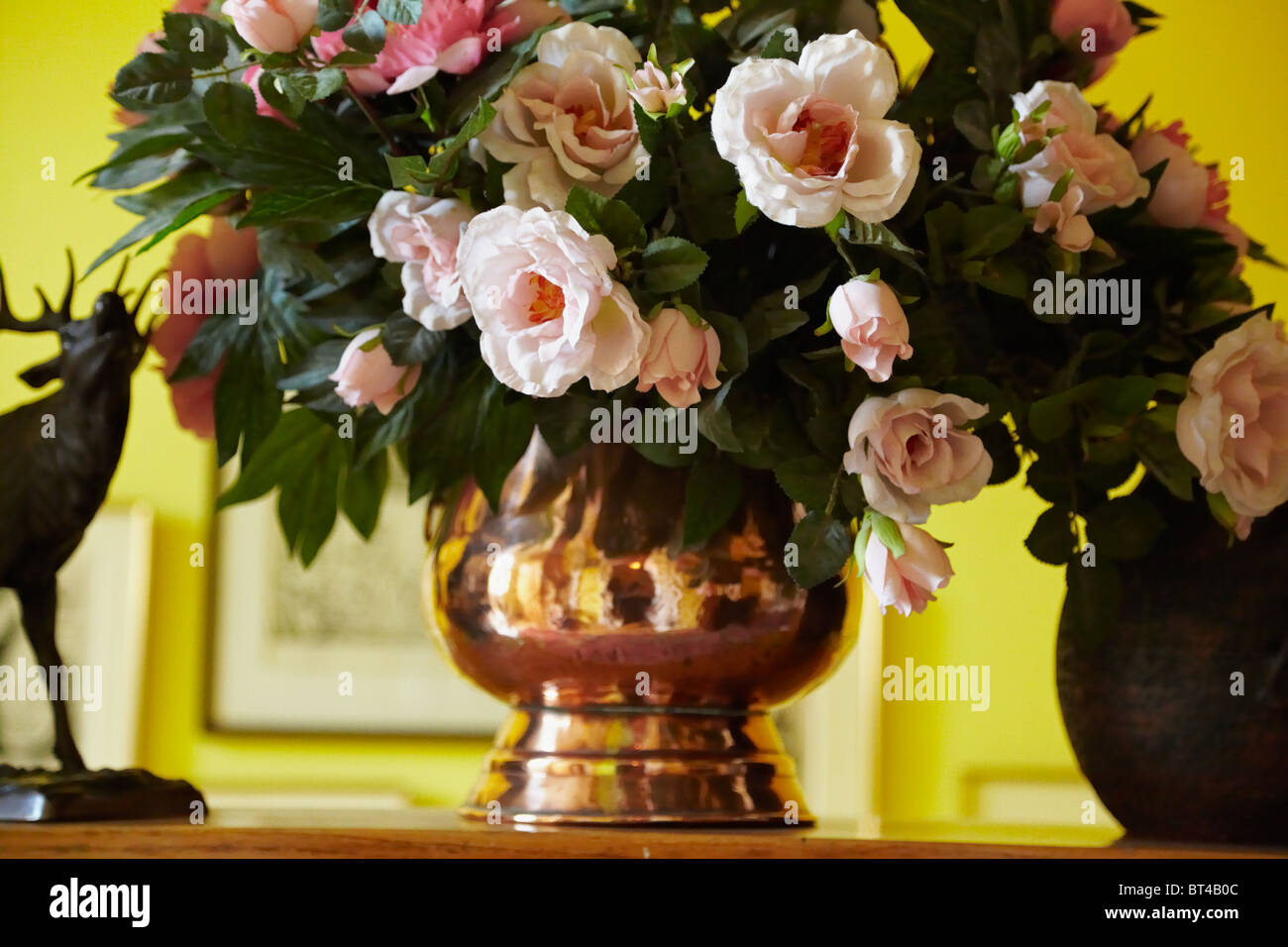 Still life with a bouquet of peony fake flowers in an old copper still life with a bouquet of peony fake flowers in an old copper vase on a shelf indoor interior shot izmirmasajfo