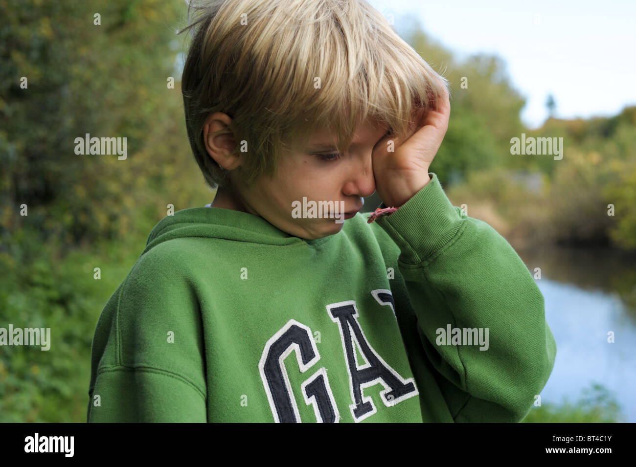 Sad, tired and tearful blond-haired little boy in a green top standing outside alone after being bullied and picked - Stock Image