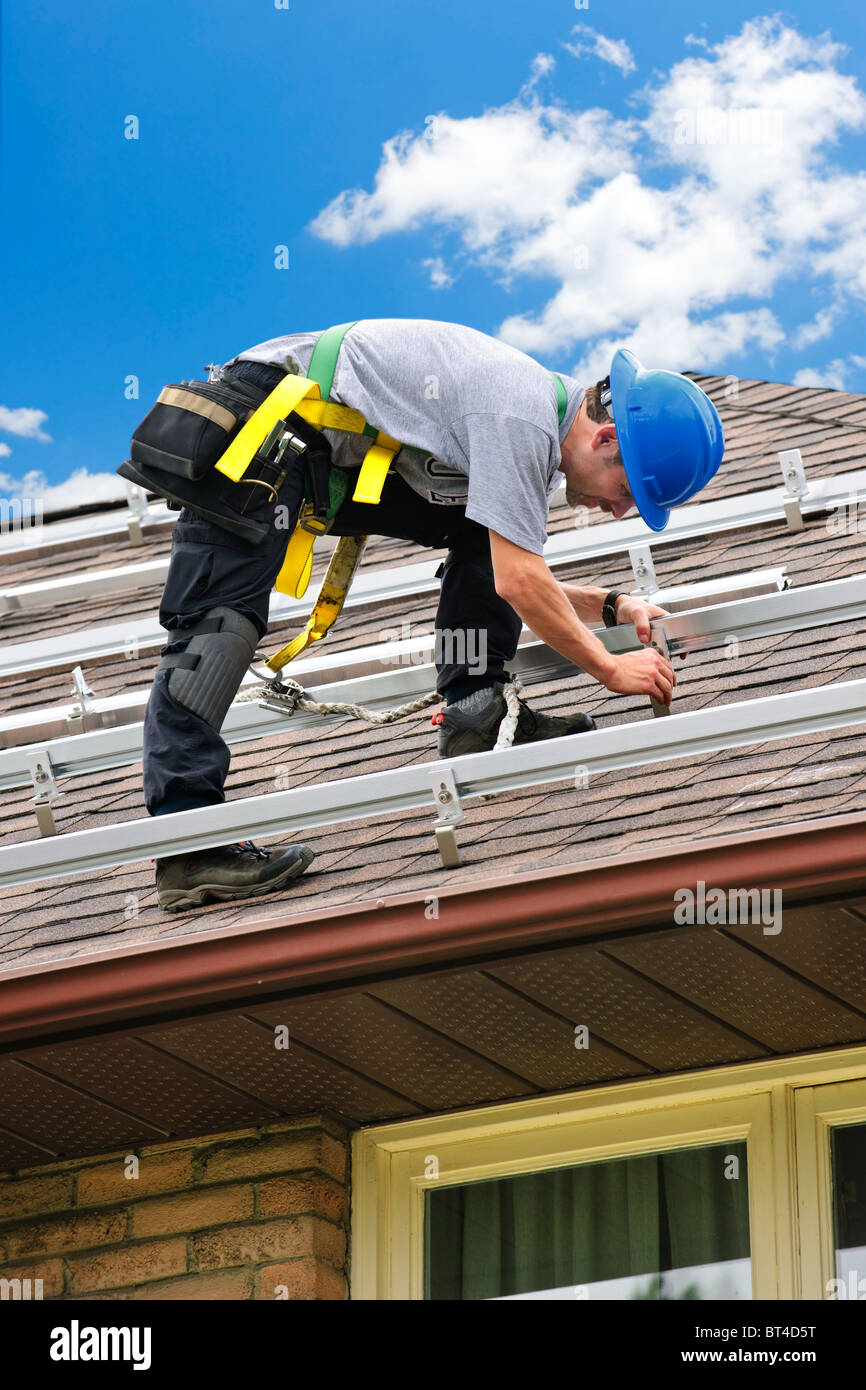 Man installing rails for solar panels on residential house roof - Stock Image