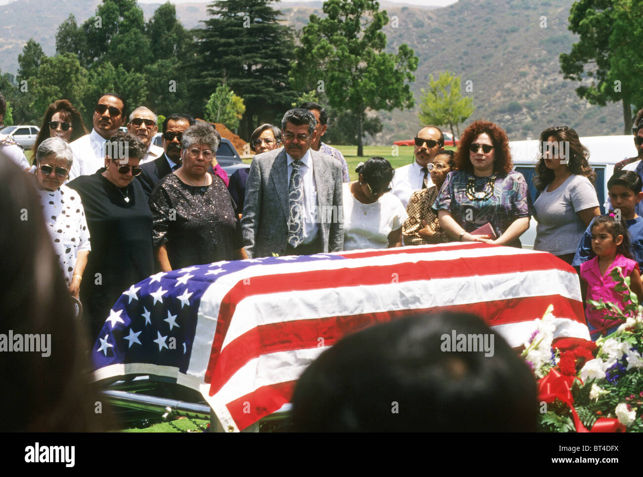 Hispanic family funeral burial cemetery ceremony rite dead death pass away sad grief cry weep love flag drape casket - Stock Image