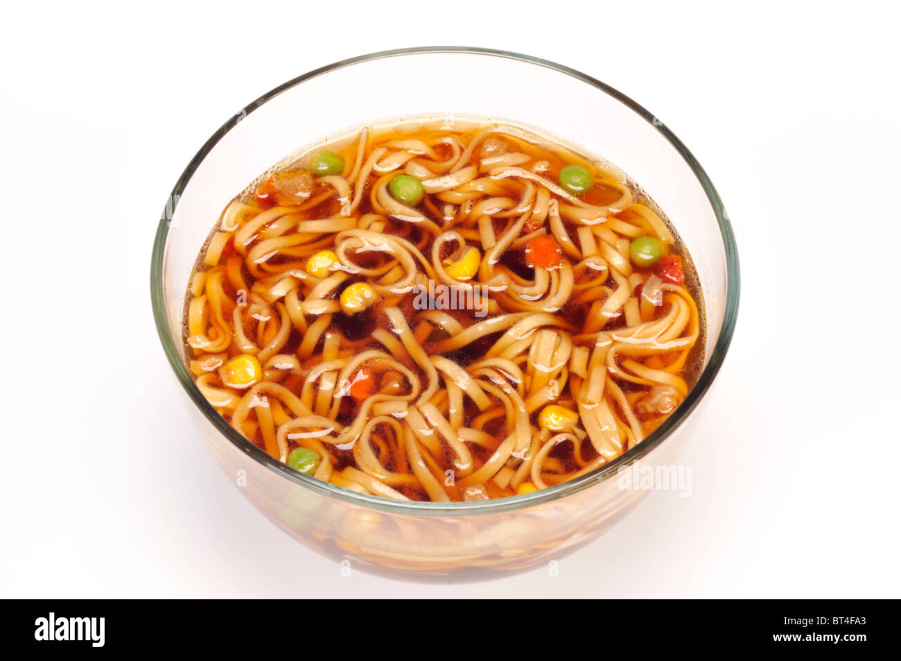 Glass bowl of cooked chinese ramen noodle oriental flavor soup on white cut out. - Stock Image