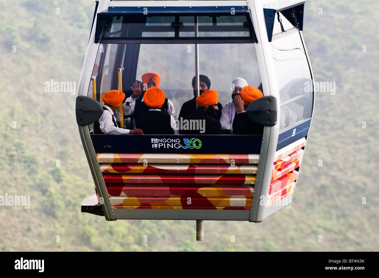 A cable car full of Sikh tourist on its way to the Big Buddha on Lantau island in Hong Kong. - Stock Image