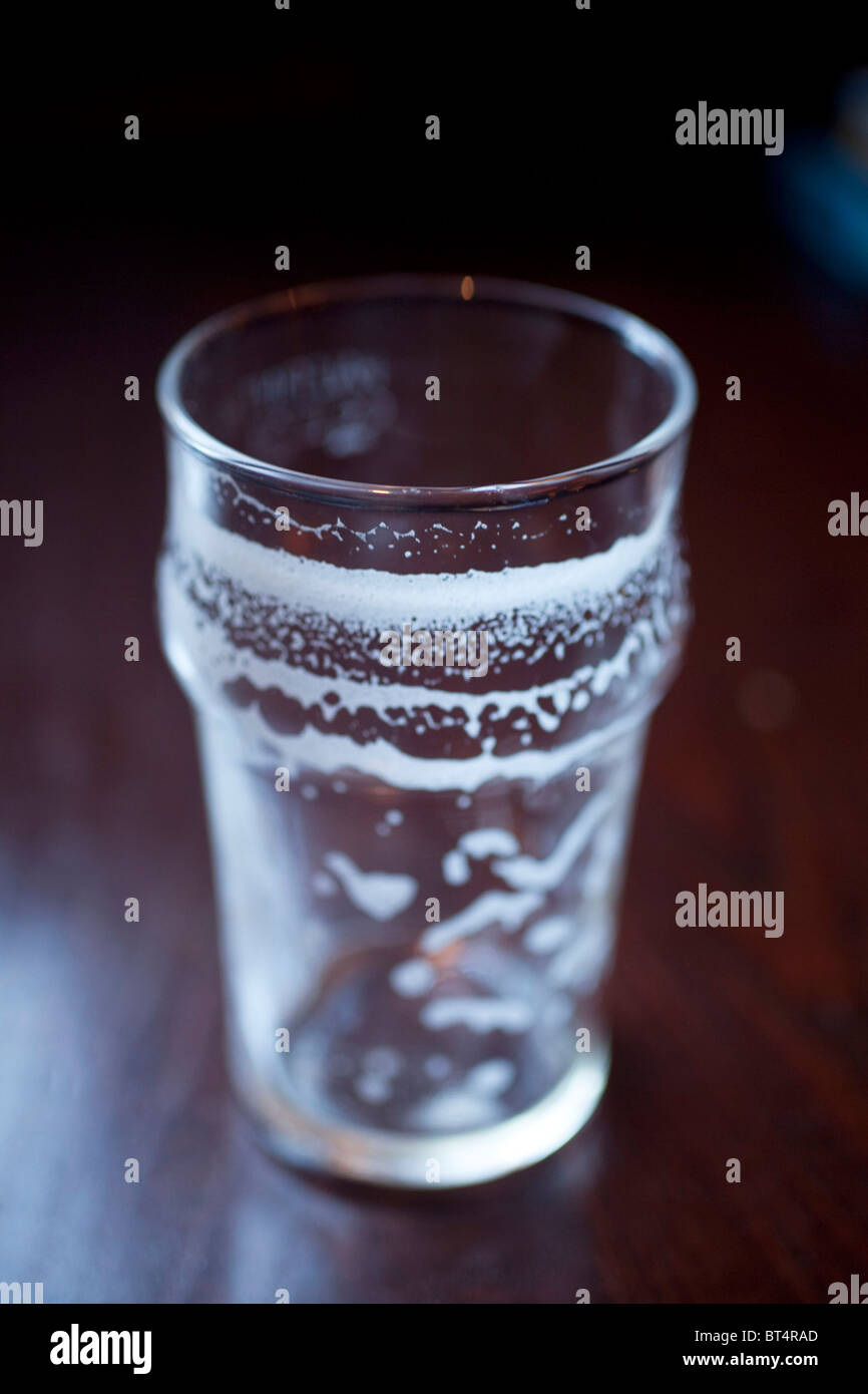 Empty pint glass on a pub table - Stock Image