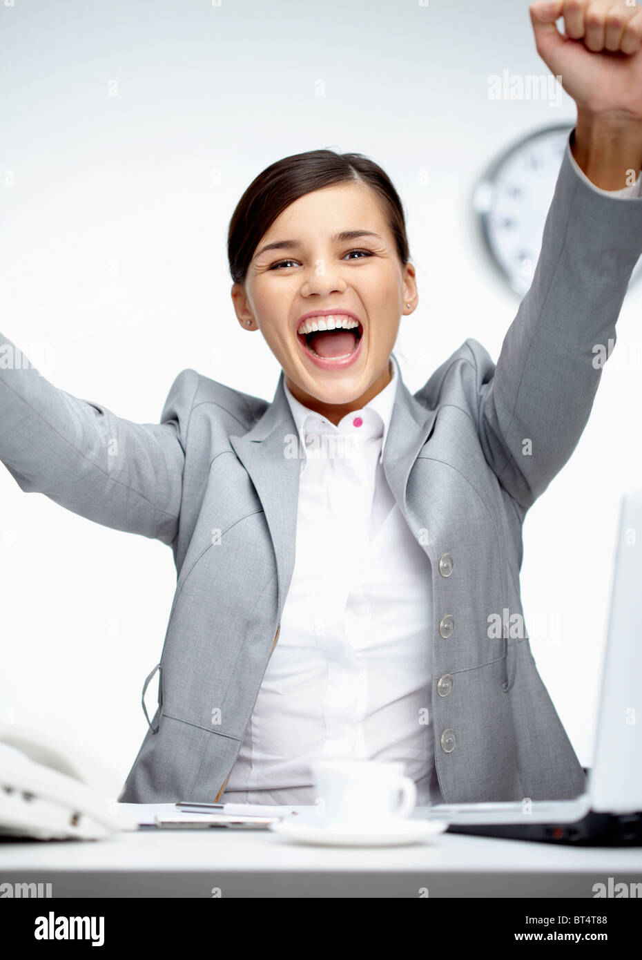 Image of young businesswoman shouting in gladness with raised arms - Stock Image