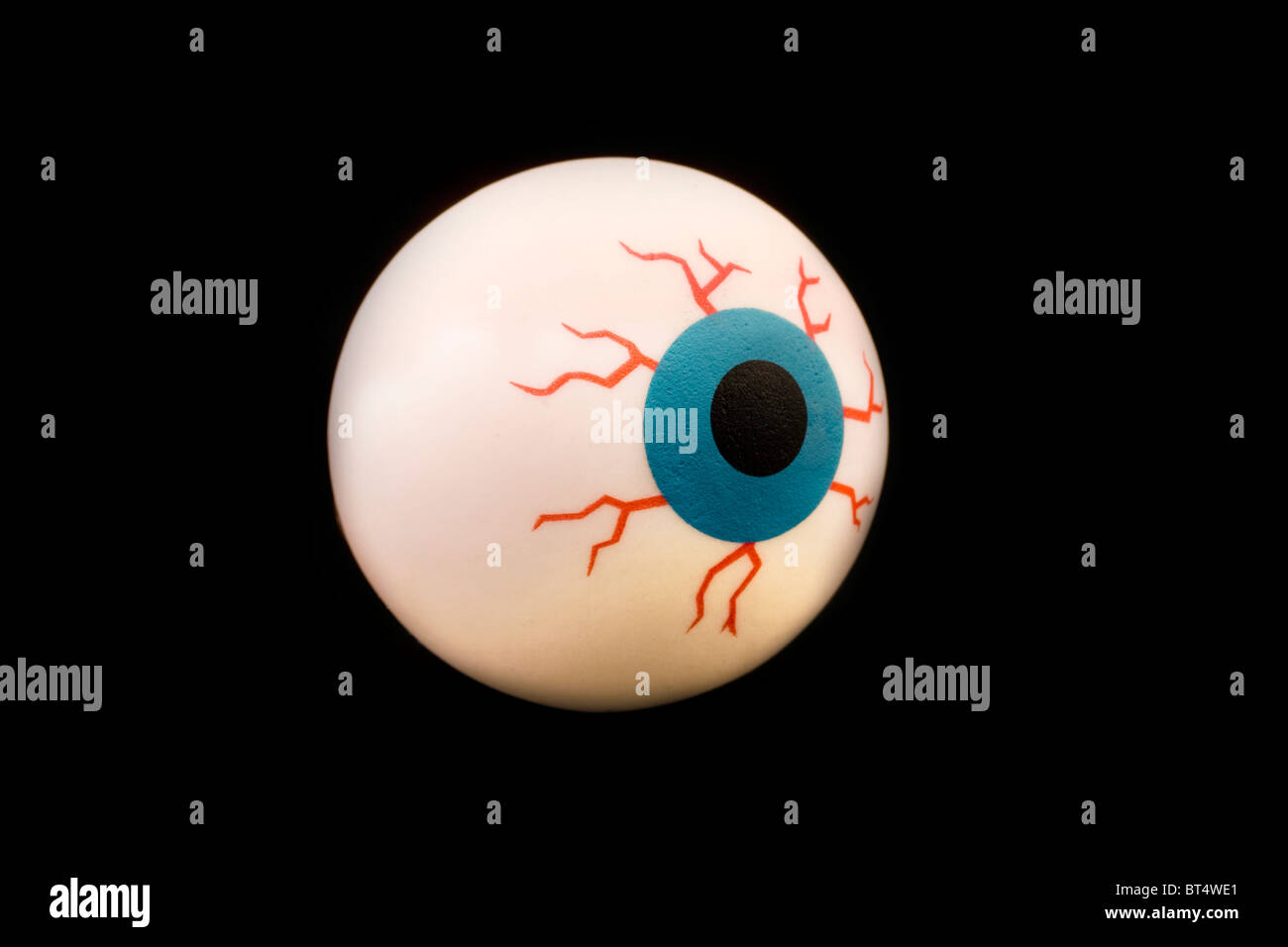 rubber toy eyeball isolated on a black background - Stock Image
