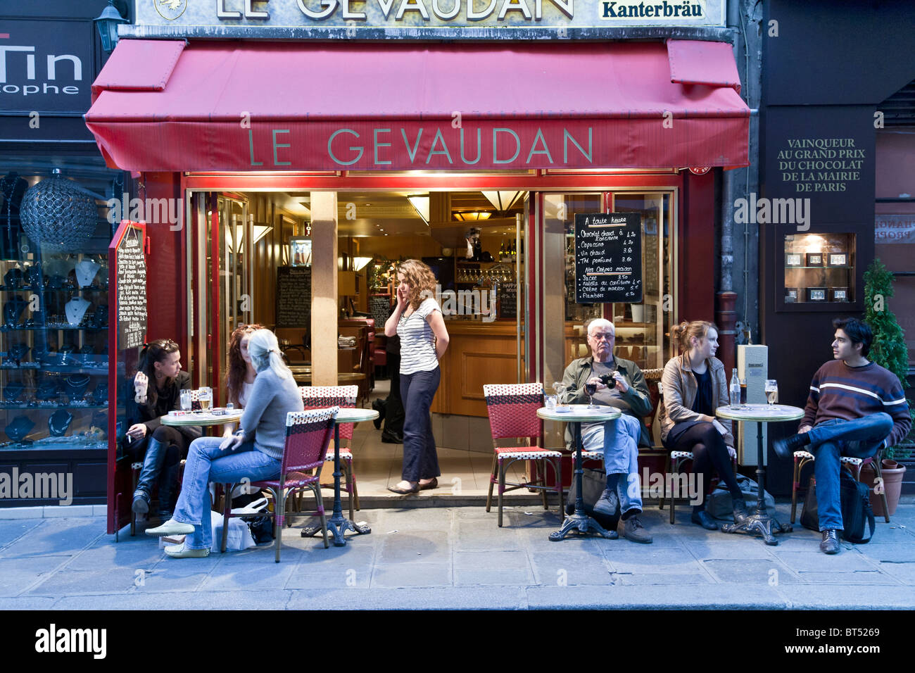 diverse French young  people & one senior American man sitting relaxing at outdoor seating small sidewalk cafe Rue Stock Photo