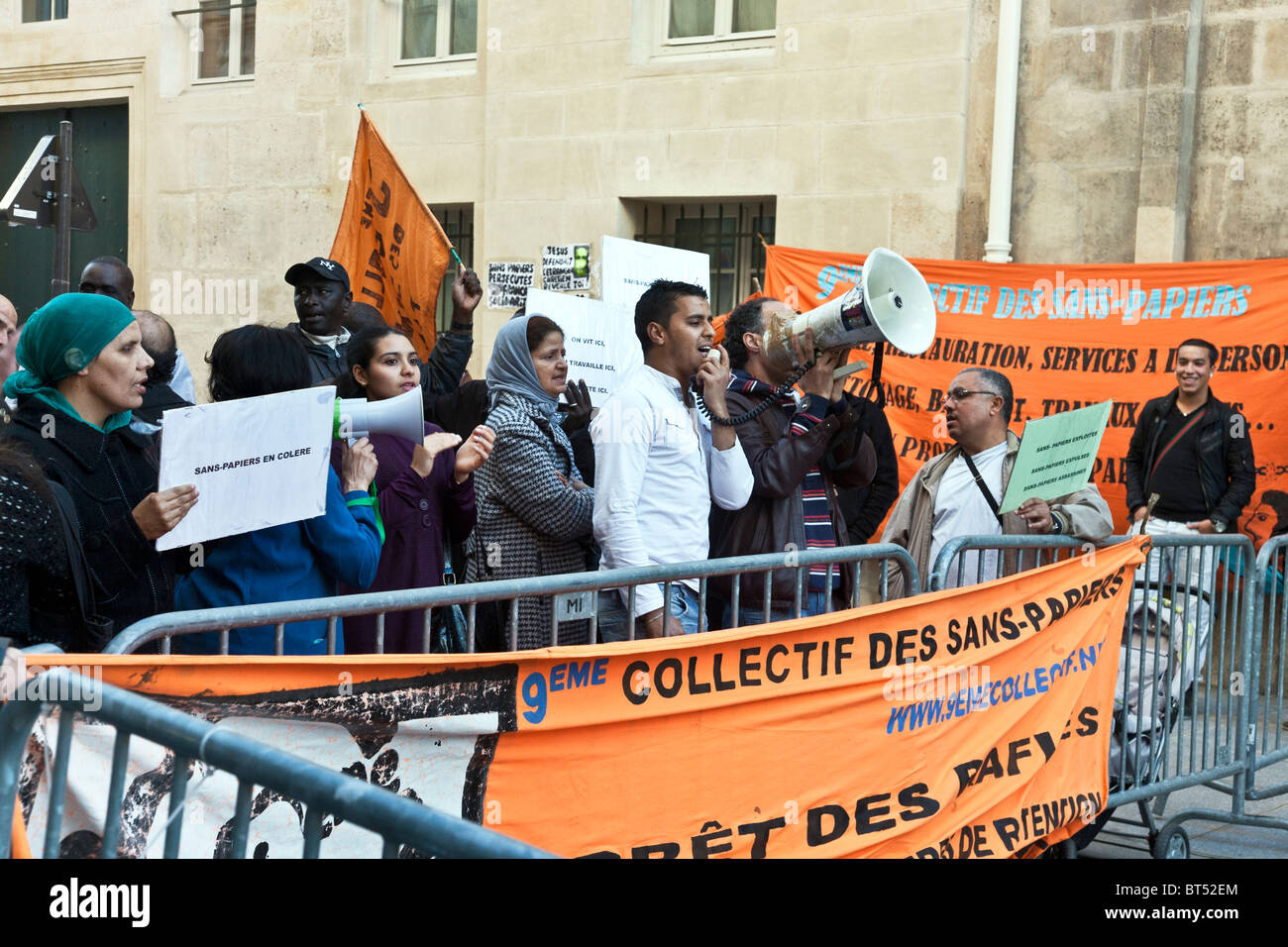 small diverse group of undocumented workers without identity papers demonstrate against persecution singing & - Stock Image
