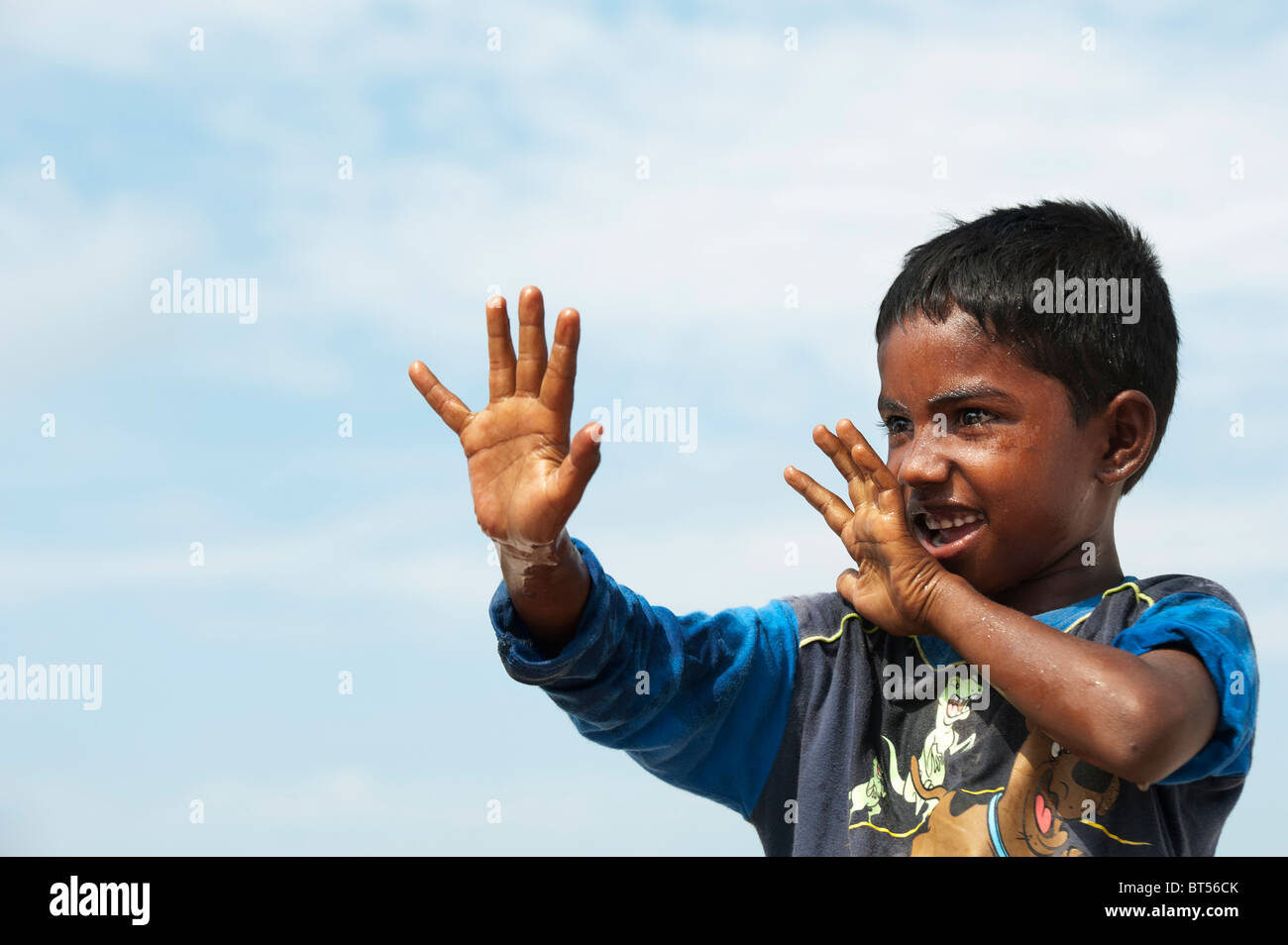 Indian boy just before being splashed with water. India - Stock Image