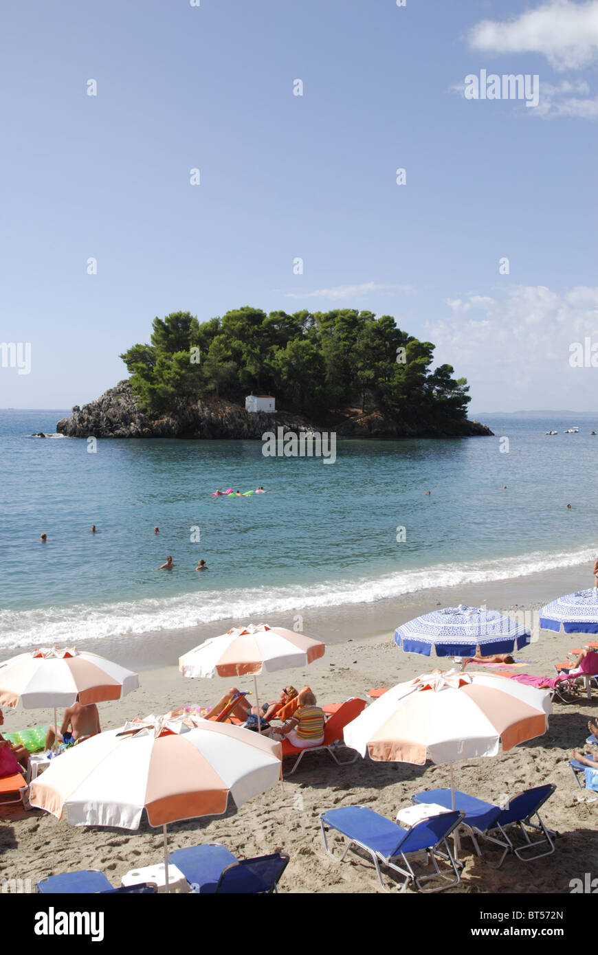 Kryoneri Beach at Parga, Epirus, Greece with sunbathers and swimmers. Panagia Island in the background. - Stock Image
