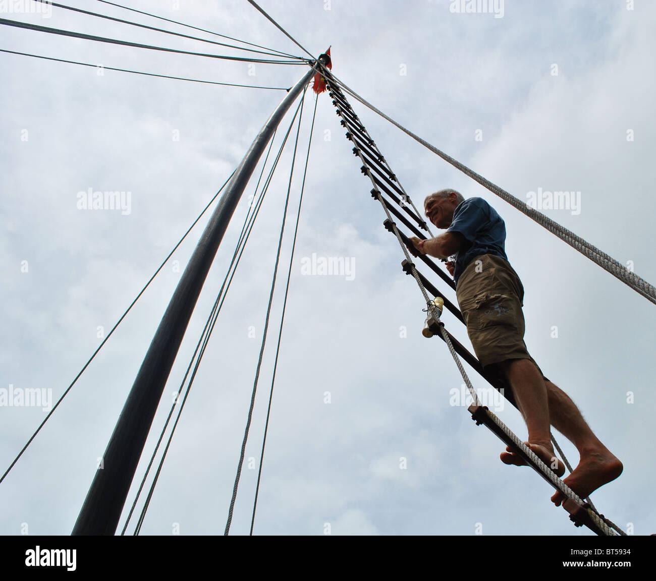 Man climbing rigging of Junk, Vietnam - Stock Image