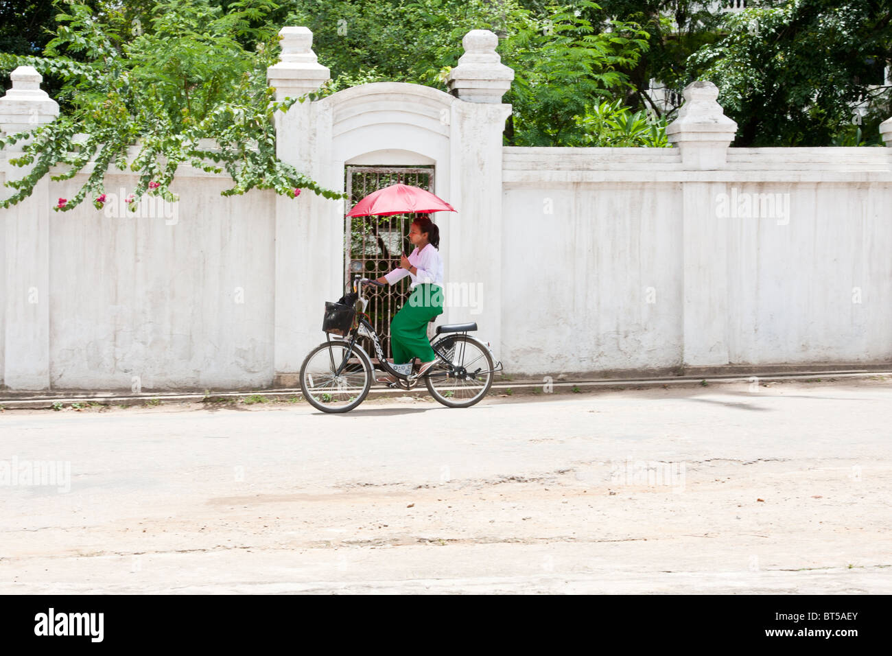 A  Burmese student rides her bike past a white wall in Chiang tong, Myanamar Stock Photo