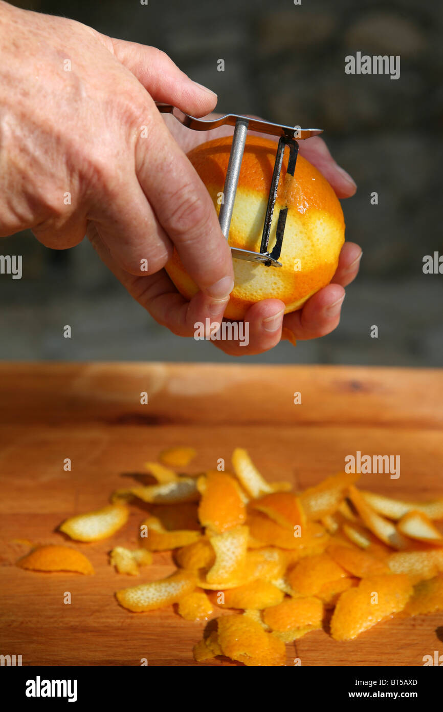 Peeling the rind of an orange. - Stock Image