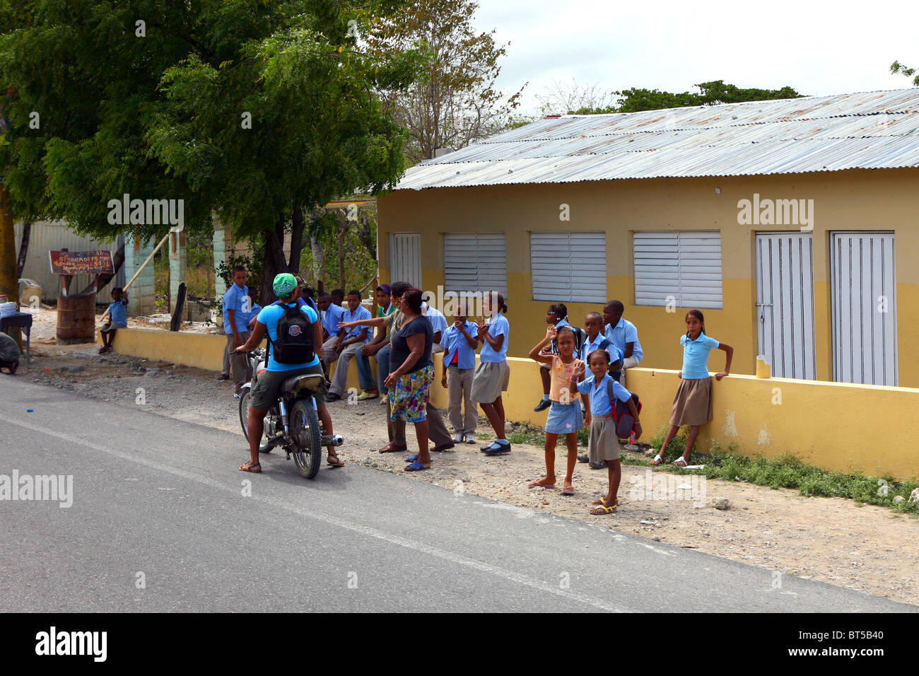 Group on young Dominican school children all dressed in uniform waiting outside their school. One child is on a - Stock Image