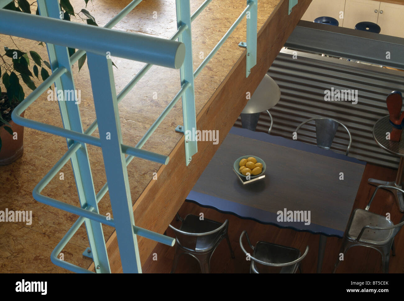 Birdseye view from gallery with pale blue metal banisters of metal table in modern loft conversion dining room Stock Photo